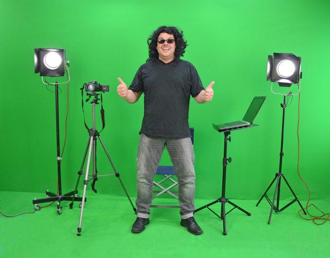 Mann vor einer grünen Wand, um ihn herum Equipment von einem Fotostudio