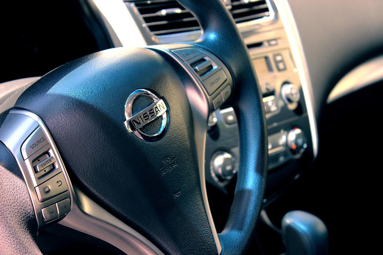 Ein Auto Cockpit mit Lenkrad. Das Lenkrad trägt die aufschrift Nissan.