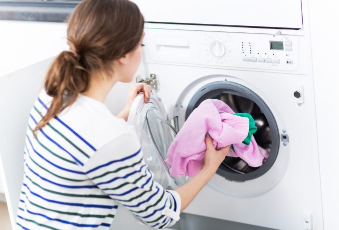 Junge Frau legt Wäsche in die Waschmaschine